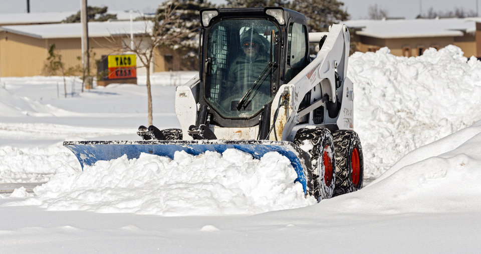 Photo - Crews work to clear snow from the parking lot of the The Market at Czech Hall in Oklahoma City, Okla. on Wednesday, Feb. 17, 2021.  [Chris Landsberger/The Oklahoman]