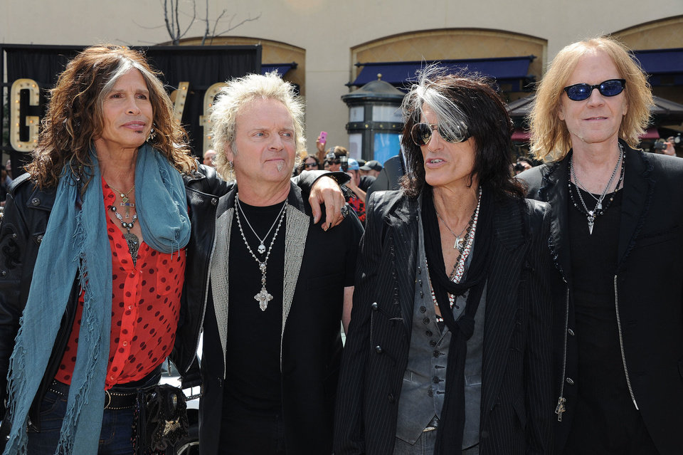 Photo - Steven Tyler, from left, Joey Kramer, Joe Perry, and Tom Hamilton of Aerosmith, pose for pictures at the Aerosmith news conference announcing the 2012 Global Warming Tour, Wednesday, March 28, 2012, at The Grove, in Los Angeles. The Global Warming Tour will play 18 markets beginning on June 16, in Minneapolis. (AP Photo/Katy Winn) ORG XMIT: CAKW101
