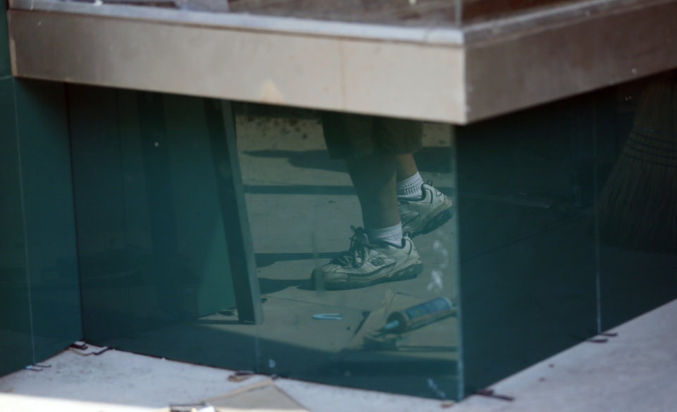 Photo -  Hank Falkenberg's feet are reflected in Vitrolite installed at the Tower Theater. Vitrolite is a type of glass tile that was popular in the 1920s and 1930s, but it is no longer produced. [Photo by Nate Billings, The Oklahoman]