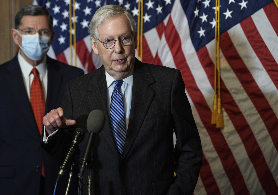 "Photo -  Senate Majority Leader Mitch McConnell speaks during a news conference with other Senate Republicans on Dec. 15 on Capitol Hill in Washington, while Sen. John Barrasso, R-Wyoming, listens at left. ""There will be another major rescue package for the American people,"" McConnell said Sunday in announcing an agreement for a relief bill that would total almost $900 billion. [Nicholas Kamm/Pool Photo via AP]"