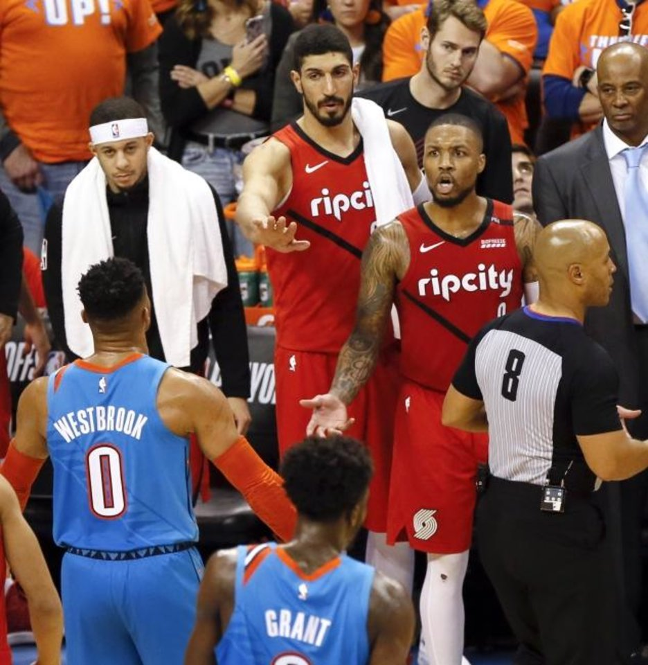 Photo -  Oklahoma City's Russell Westbrook (0) and Portland's Damian Lillard (0) continue to exchange pleasantries after Lillard left Friday's Game 3 as former Thunder player Enes Kanter, middle, tries to ease the tension late in the Thunder's 120-108 win. [Nate Billings/The Oklahoman]