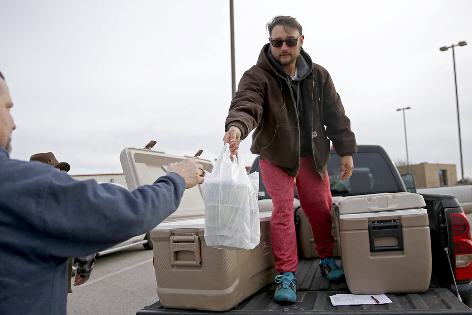 Photo - Andrew Graves with The Farm on Fishmarket hands a customer an order at the Cleveland County Fairgrounds in Norman, Okla., Saturday, March 21, 2020. The weekly Norman Farm Market was closed to walk up business but customers were able to pick up orders placed in advance. [Bryan Terry/The Oklahoman]