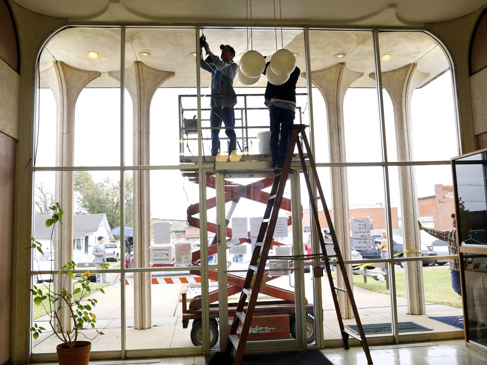 Photo - Workers remove a large pane of a broken window on the front of the Cushing City Hall. Damage in downtown Cushing on Monday, Nov. 7, 2016, caused by Sunday night's 5.0 magnitude earthquake. Photo by Jim Beckel, The Oklahoman