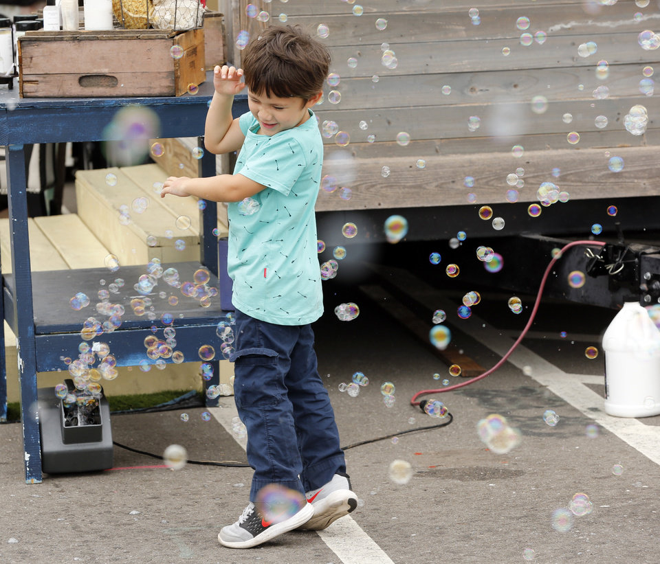 Photo -  Sunny Fox plays in a bubble in front of the Lathe Soap Shop at the Oklahoma State Fair on Thursday.