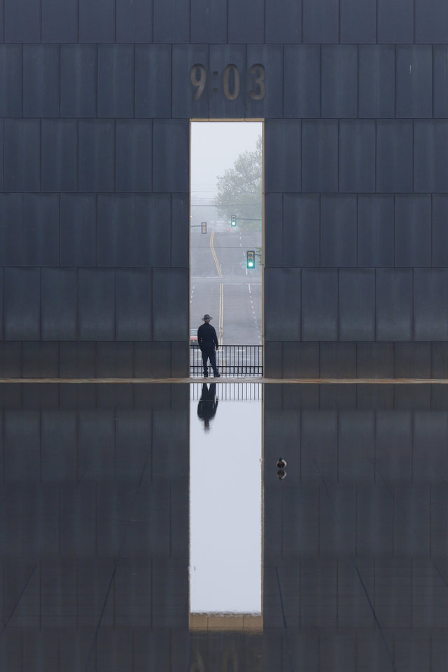 Photo - A security guard stands watch inside the Oklahoma City National Memorial and Museum on the 25th anniversary of the bombing of the Alfred P. Murrah Federal Building, in Oklahoma City, Sunday, April 19, 2020. The memorial remains closed and did not hold a live remembrance ceremony because of the coronavirus pandemic. [Doug Hoke/The Oklahoman]