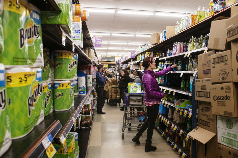 Photo -  Customers shop for cleaning products as City Market employees restock shelves in Aspen, Colo. on Thursday, March 12, 2020. [Kelsey Brunner/The Aspen Times via AP]