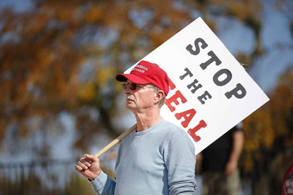 Photo - Craig Deatherage holds a sign during a rally for President Trump at the Oklahoma state Capitol in Oklahoma City,  Saturday, Nov. 7, 2020. [Sarah Phipps/The Oklahoman]