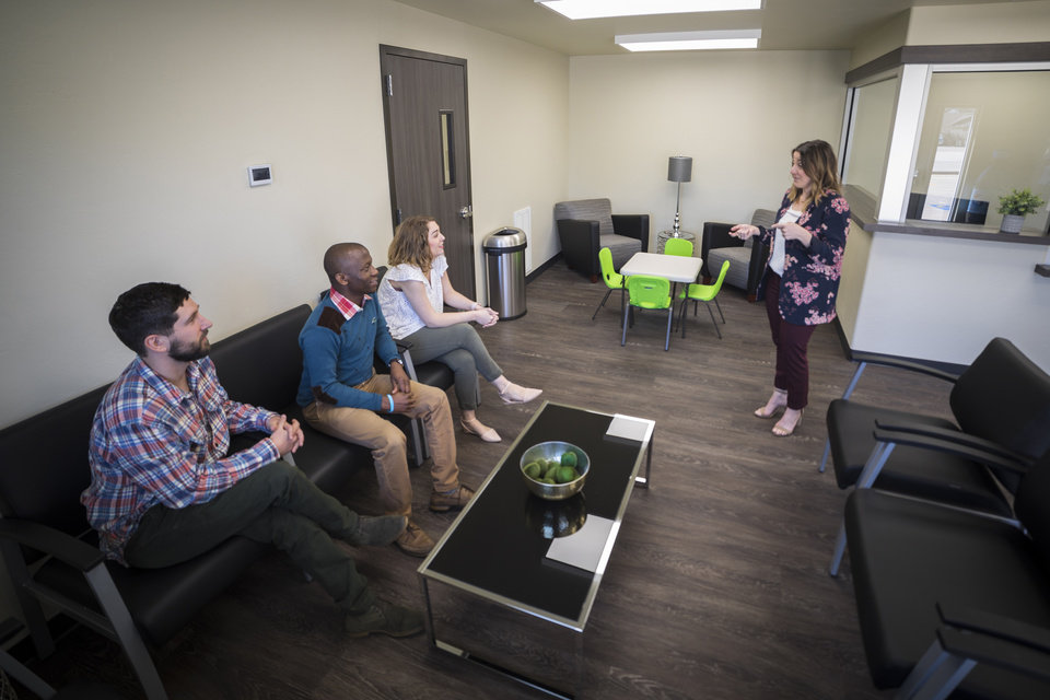 Photo - Dr. Tara Signs (standing), marriage and family therapy clinical director at OBU, visits with MFT students (left to right) Scott Pfister, Ronald Assimwe and Hannah Mire in the lobby of OBU's new Marriage and Family Therapy Clinic. Photo provided by OBU.