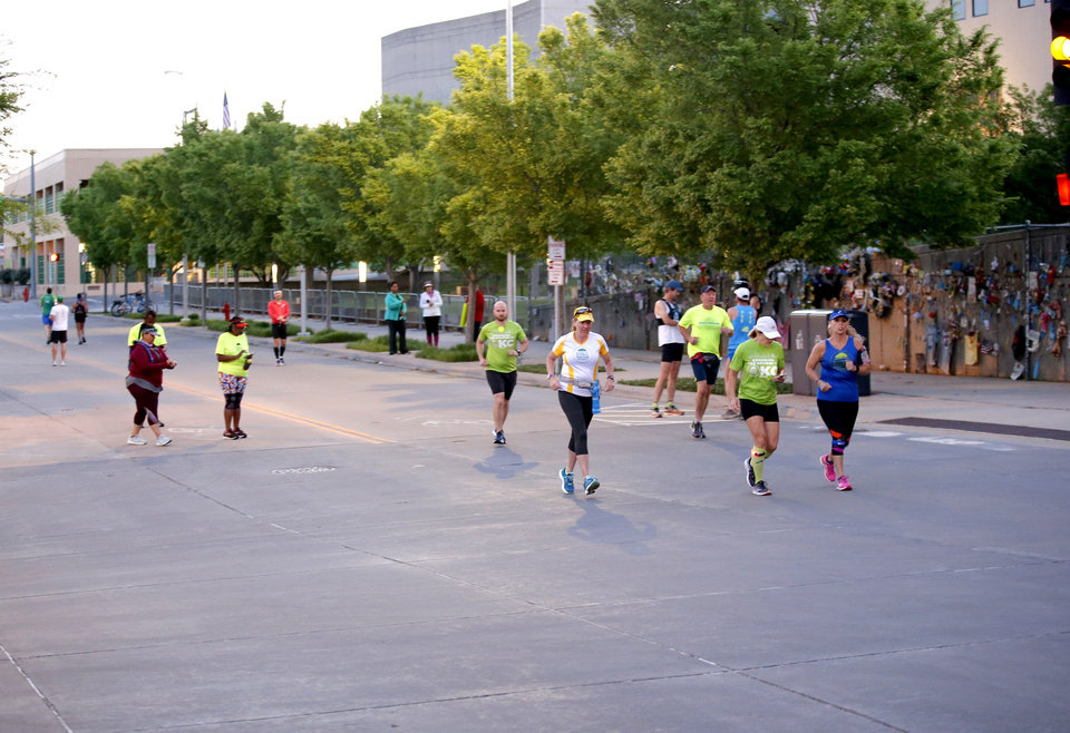 Photo - Runners run the route of the Oklahoma City Memorial Marathon in Oklahoma City,  Sunday, April 26, 2020.  The 20th Oklahoma City Memorial Marathon was delayed until October because of Covid-19. [Sarah Phipps/The Oklahoman]