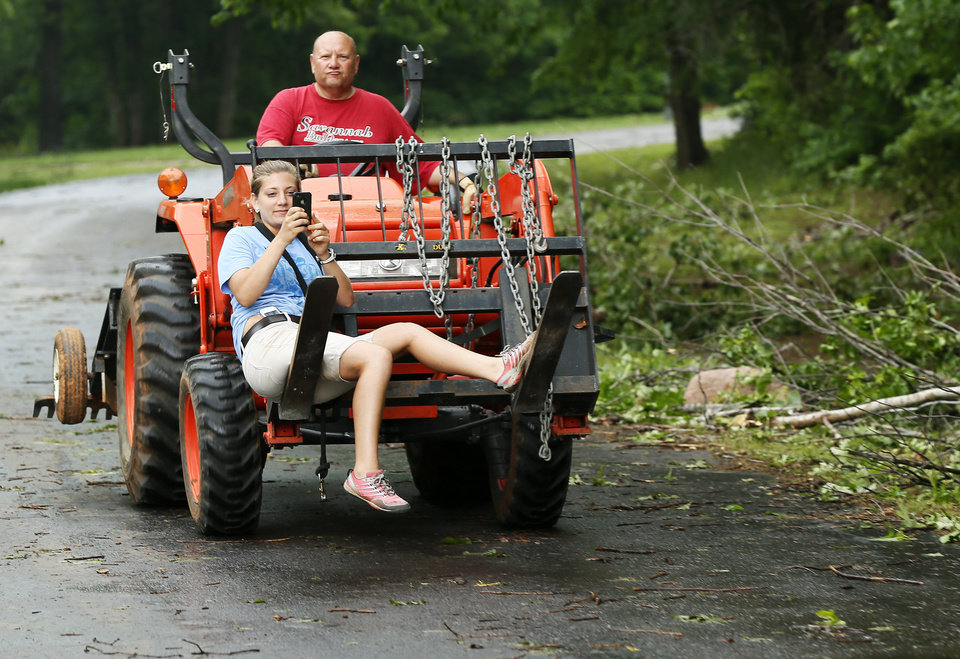 Photo - Becca Gilles rides in the front of a Kubota tractor driven by her father, Mike Gilles, as they travel to help their neighbors in the Timberlake Estates neighborhood to clean up after a tornado moved through Edmond, Okla., Sunday, May 19, 2013. Photo by Nate Billings, The Oklahoman