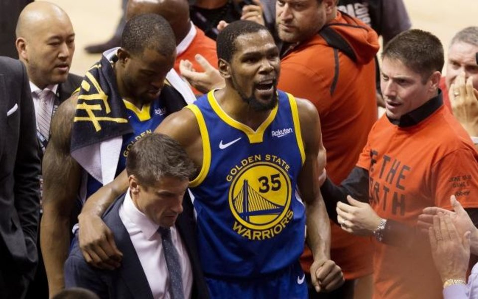 Photo -  Kevin Durant (35) limps off the court sustaining an Achilles injury during the first half of Game 5 of the NBA Finals on Monday. [Chris Young/The Canadian Press via AP]