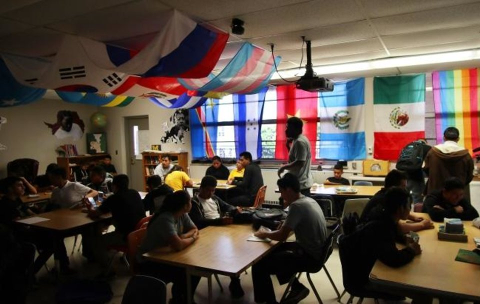 Photo -  In a class at Northwest Classen High that has numerous immigrant students, teacher Eric Parker has a flag representing each one. [Doug Hoke/The Oklahoman]