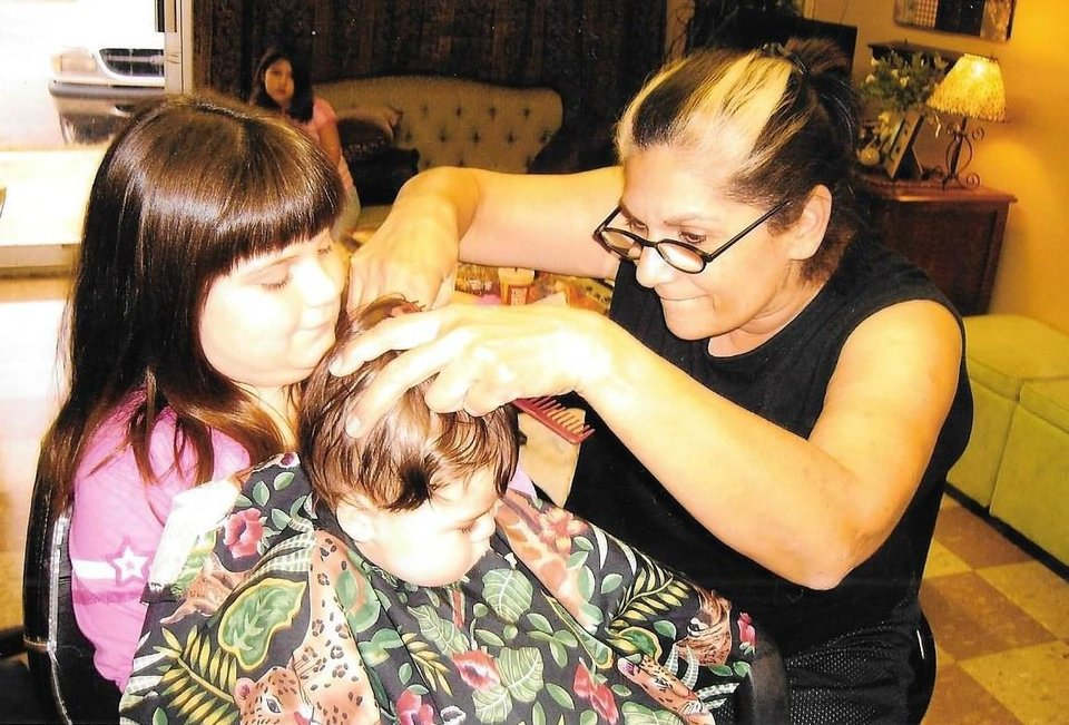 Photo - Reed cutting the hair of one of her grandchildren. Photo provided.