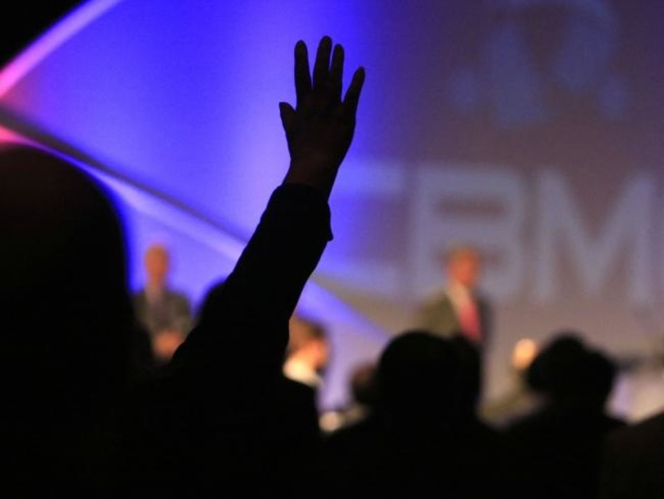 Photo -  An attendee raises his hand in worship at the 2016 CBMC Metro Prayer Breakfast at the Cox Convention Center in Oklahoma City. [Oklahoma Archives]