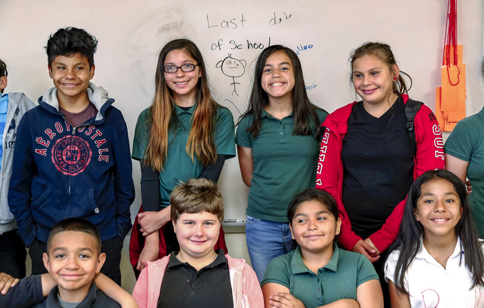 Photo - Fifth grade students in Judy Pursell's class smile as they stand with classmates for a group photo in Pursell's classroom on the last day of school at Fillmore Elementary School in southwest Oklahoma City on Tuesday, May 30, 2017. Pursell  is retiring after 26 years as an educator with Oklahoma City Public Schools District. Pursell also taught students at at Pierce Elementary School before moving to Fillmore.   Photo by Jim Beckel, The Oklahoman