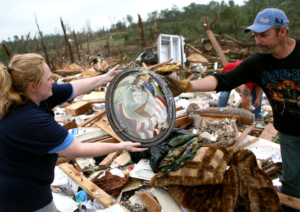Photo - Shelley Heston Bolles passes a picture to her husband Keith Bolles as they clean up at the site of their home in Little Axe, Oklahoma on Tuesday, May 11, 2010. By John Clanton, The Oklahoman