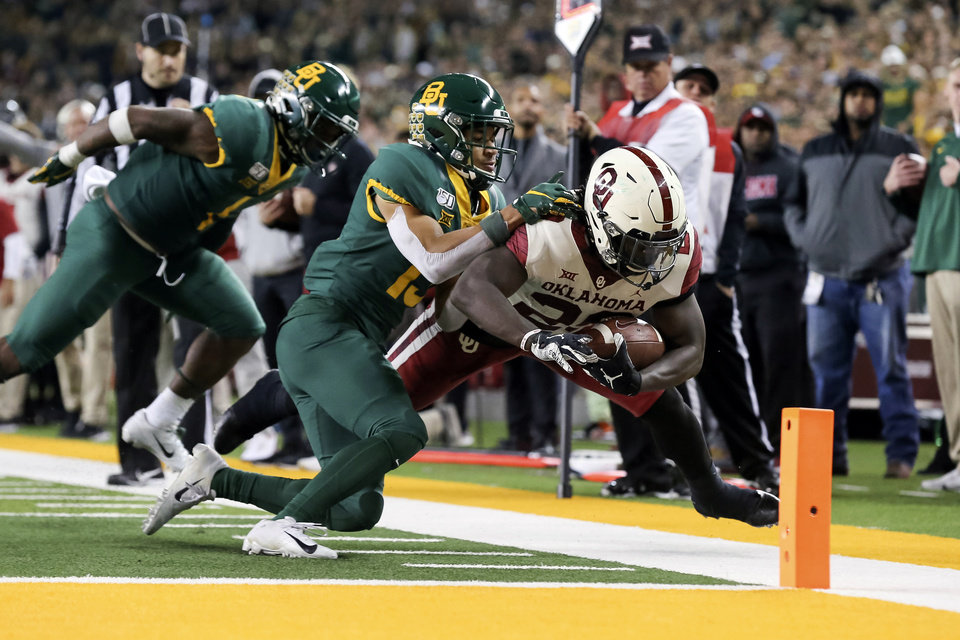 Photo - Oklahoma running back Rhamondre Stevenson, right, is pushed out of bounds by Baylor cornerback Raleigh Texada, center, during the second half of an NCAA college football game in Waco, Texas, Saturday, Nov. 16, 2019. Oklahoma won 34-31. (AP Photo/Ray Carlin)