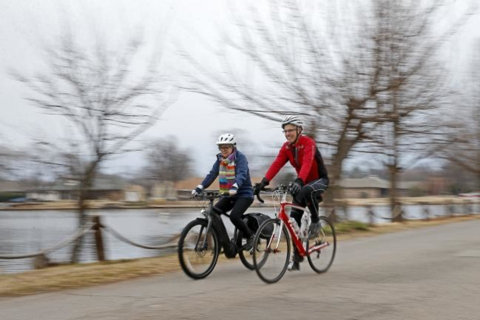 Photo -  Maryjo Meacham rides her e-bike beside Russell Pace in Oklahoma City on Tuesday. [BRYAN TERRY/THE OKLAHOMAN]