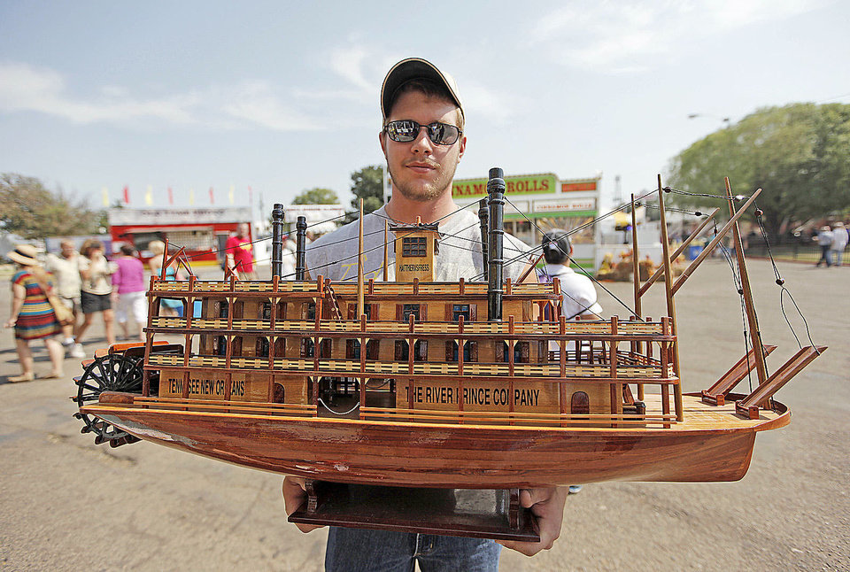 Photo - Colton Allen, of Ada, holds a boat that his uncle bought at the Oklahoma State Fair in Oklahoma City, Friday, Sept. 21, 2012.  Photo by Garett Fisbeck, The Oklahoman
