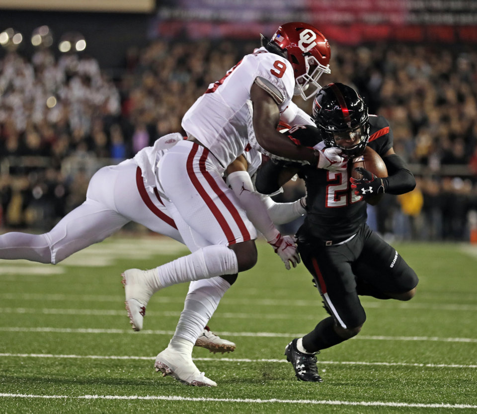 Photo - Texas Tech's Ta'Zhawn Henry (26) is tackled by Oklahoma's Kenneth Murray (9) during the first half of an NCAA college football game Saturday, Nov. 3, 2018, in Lubbock, Texas. (AP Photo/Brad Tollefson)