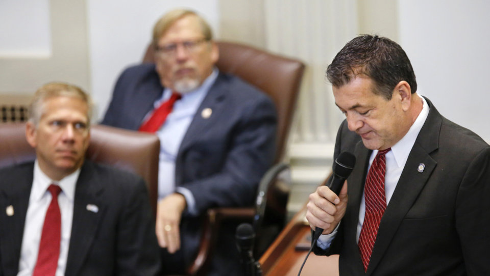 Photo -  Rep. Dan Kirby talks in quiet tones to fellow legislators on Tuesday. [Photo by Jim Beckel, The Oklahoman]
