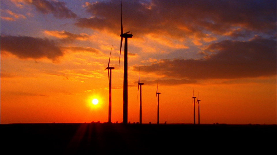 Photo -  The sun sets behind wind turbines.