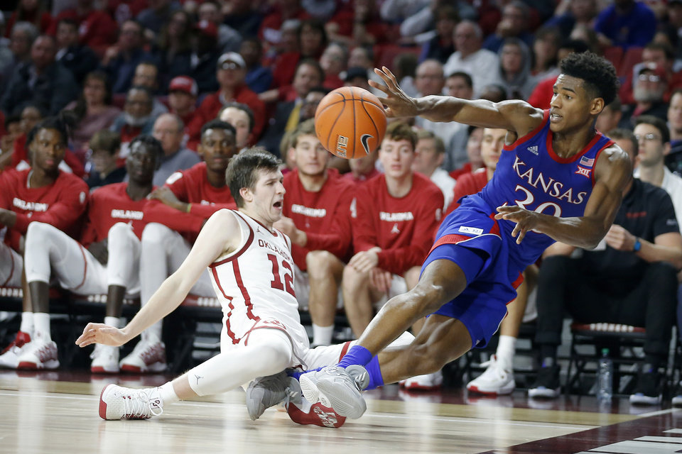 Photo - Kansas' Ochai Agbaji (30) passes over Oklahoma's Austin Reaves (12) during an NCAA college basketball game between the University of Oklahoma Sooners (OU) and the University of Kansas Jayhawks at Lloyd Noble Center in Norman, Okla., Tuesday, Jan. 14, 2020. Oklahoma lost 66-52.  [Bryan Terry/The Oklahoman]