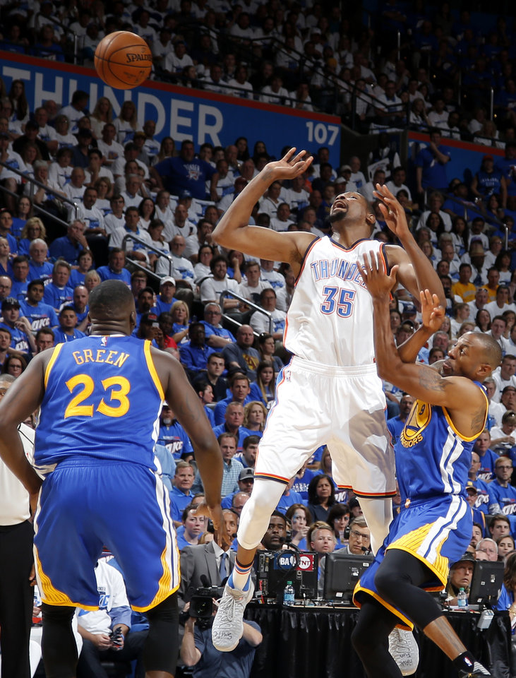Photo - Oklahoma City's Kevin Durant (35) is fouled by Golden State's Andre Iguodala (9) as Draymond Green (23) watches during Game 3 of the Western Conference finals in the NBA playoffs between the Oklahoma City Thunder and the Golden State Warriors at Chesapeake Energy Arena in Oklahoma City, Sunday, May 22, 2016. Oklahoma City won 133-105. Photo by Bryan Terry, The Oklahoman