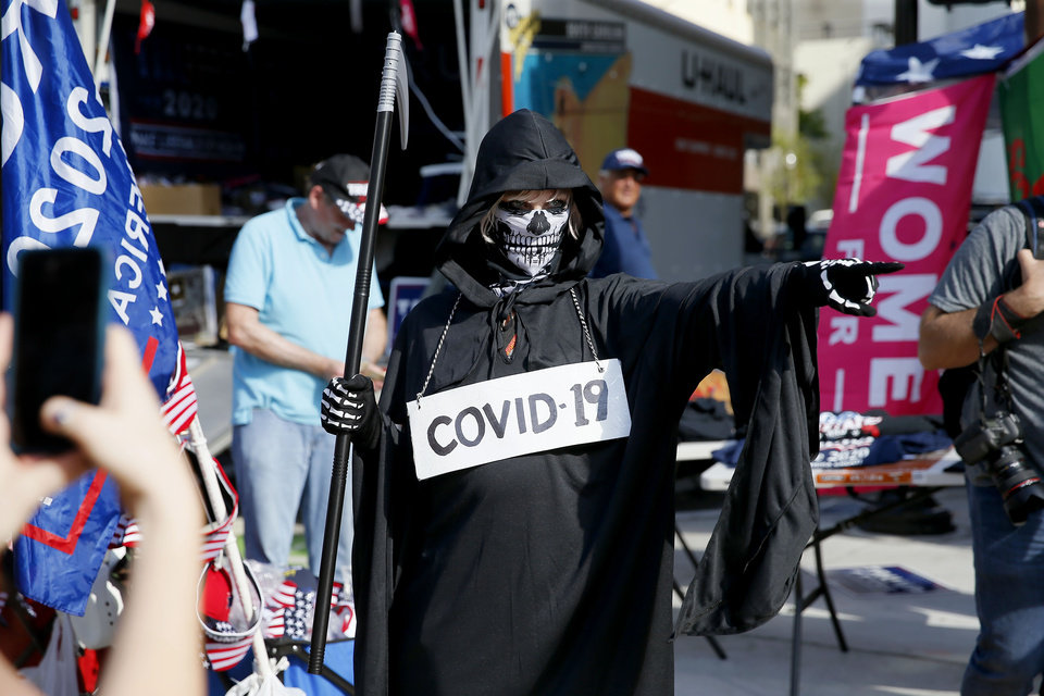 Photo - A person dressed as the Grim Reaper points at the crowd outside the President Donald Trump rally at the BOK Center in Tulsa, Okla., Saturday, June 20, 2020. [Bryan Terry/The Oklahoman]