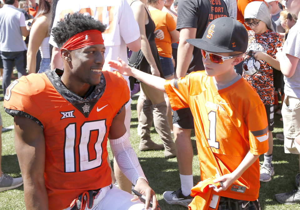 Photo - Oklahoma State's Tyrell Alexander (10) talks with fan Cash Codaren, 9, during the Oklahoma State Cowboys spring practice at Boone Pickens Stadium in Stillwater, Okla., Saturday, April 20, 2019.  Photo by Sarah Phipps, The Oklahoman