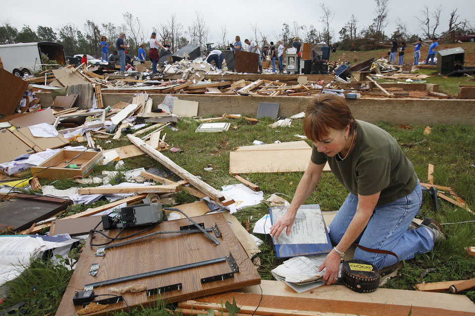 Photo - Administrative assistant LaDonna Cockerham sieved through the debris of her office at the Little Axe School Central Office, Tuesday, May 11, 2010. The school was hit by a tornado Monday, May 10, 2010. Photo by David McDaniel, The Oklahoman