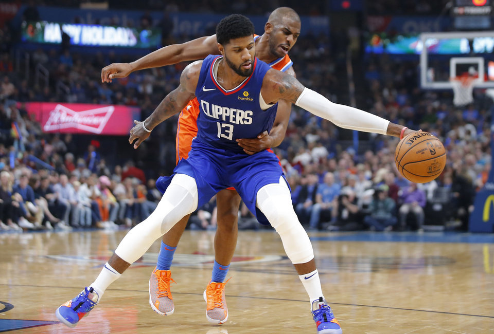 Photo - Oklahoma City's Chris Paul (3) defends LA's Paul George (13) during an NBA basketball game between the Oklahoma City Thunder and the LA Clippers at Chesapeake Energy Arena in Oklahoma City, Sunday, Dec. 22, 2019. Oklahoma City won 118-112. [Bryan Terry/The Oklahoman]