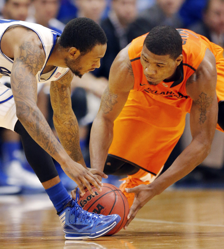 Photo - Kansas guard Naadir Tharpe, left, and Oklahoma State guard Marcus Smart, right, reach for a loose ball during the second half of an NCAA college basketball game at Allen Fieldhouse in Lawrence, Kan., Saturday, Jan. 18, 2014. Kansas defeated Oklahoma State 80-78. (AP Photo/Orlin Wagner)