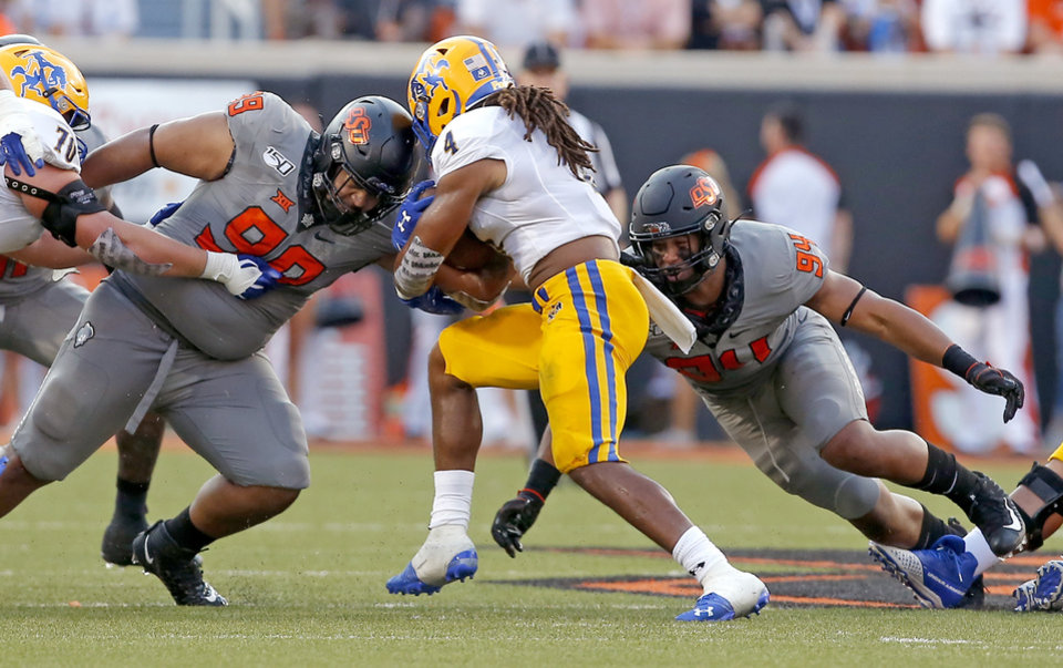 Photo - Oklahoma State's Sione Asi (99) and Trace Ford (94) tackle McNeese State's Elijah Mack (4) in the second quarter during the college football game between the Oklahoma State Cowboys and the McNeese State Cowboys at Boone Pickens Stadium in Stillwater, Okla., Saturday, Sept. 7, 2019. [Sarah Phipps/The Oklahoman]