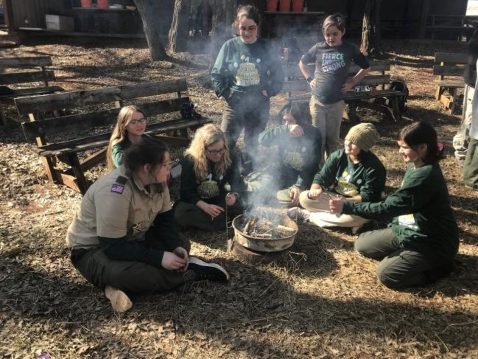 Photo -  Girls take part in a a fire-making lesson at a Scouts BSA campout at the John W. Nichols Scouts Ranch in Mustang. They are: Katie McManus, Alexa Mitchell (back), Chloe Kessler, Jessie McMcmanus (standing), Skyler Gee, Fiona Blades (standing), Faith Randell and Crystal Ballew. [Carla Hinton/The Oklahoman]