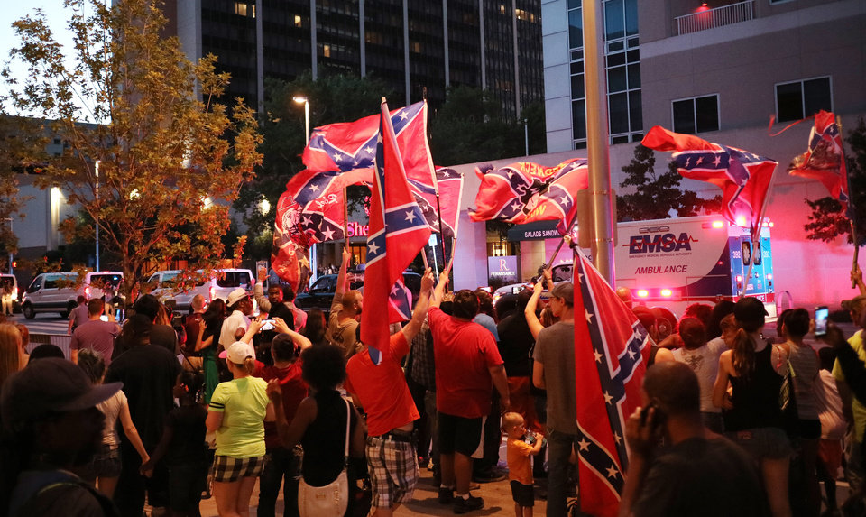 Photo - A small group of people wave flags of the Confederacy as Pres. Barack Obama's motorcade arrives in downtown Oklahoma City, Wednesday, July 15, 2015. Photo by Doug Hoke, The Oklahoman