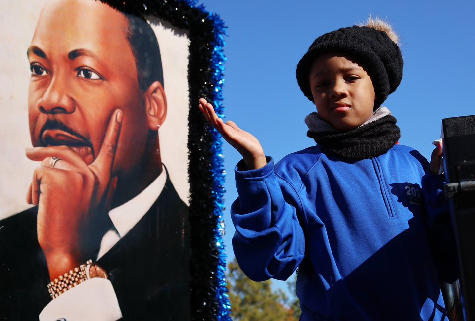 Photo - A young girl waves to the crowd from a float with a poster of Dr. King at the MLK Day Parade during celebration of Dr. Martin Luther King, Jr. holiday, Monday, January 20, 2019. [Photo by Doug Hoke/The Oklahoman]