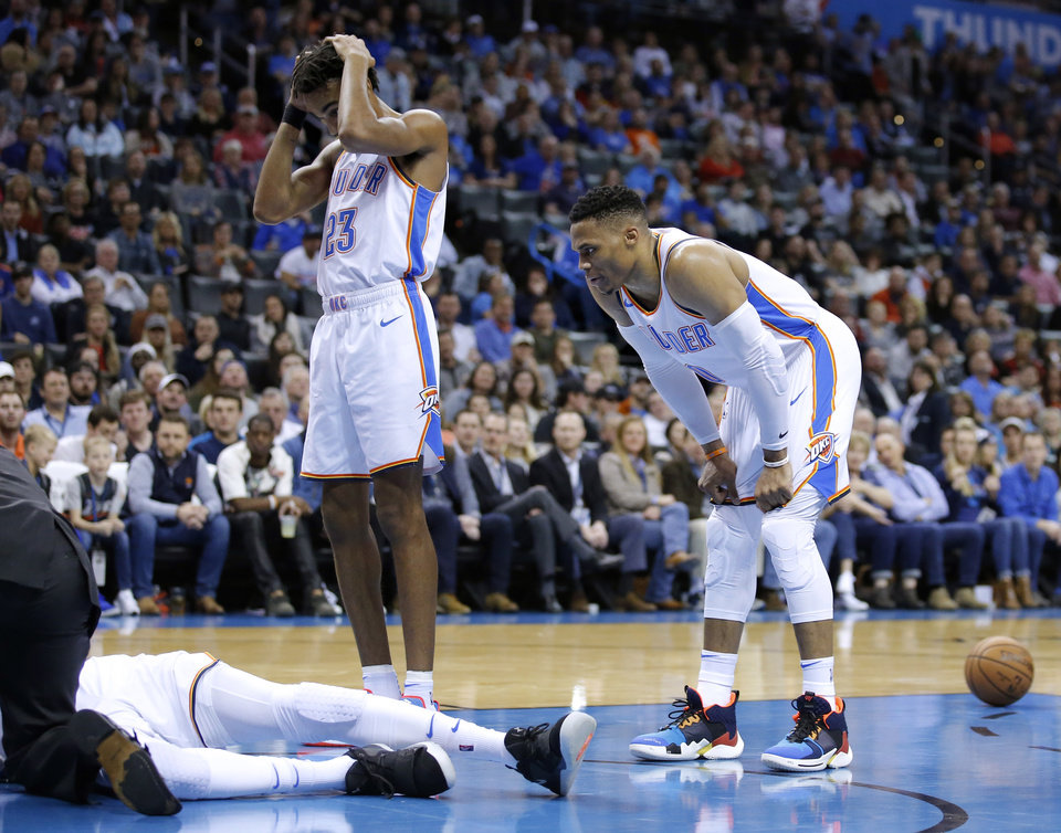 Photo - Oklahoma City's Terrance Ferguson (23) and Russell Westbrook (0) react as medical personal attend to Oklahoma City's Nerlens Noel (3) during the NBA game between the Oklahoma City Thunder and Minnesota Timberwolves at the Chesapeake Energy Arena, Tuesday, Jan. 8, 2019. Photo by Sarah Phipps, The Oklahoman