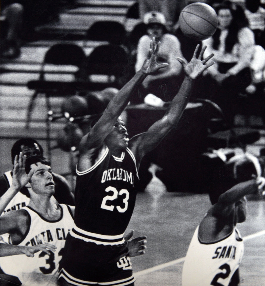 Photo - Former OU basketball player Wayman Tisdale. Oklahoma's Wayman Tisdale goes high as he receives a pass from a teammate while Santa Clara's Nick Vanos, behind, and Harold Keeling try to contain him Sunday in the Great Alaska Shootout. Photo taken unknown, photo published 11/28/1983 in The Daily Oklahoman. ORG XMIT: KOD