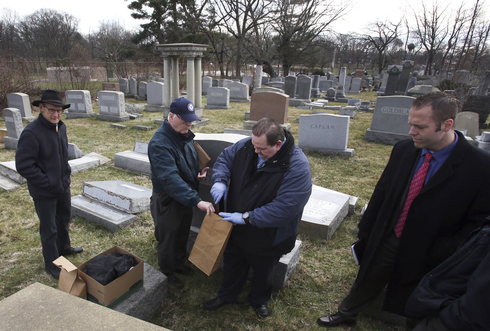 Photo - Jim McReynolds, center, from the Philadelphia Police northeast detectives unit, places items from the scene in a bag for further investigation Monday, Feb. 27, 2017, at Mount Carmel Cemetery in Philadelphia. More than 100 headstones have been vandalized at the Jewish cemetery in Philadelphia, damage discovered less than a week after similar vandalism in Missouri, authorities said. (AP Photo/Jacqueline Larma)