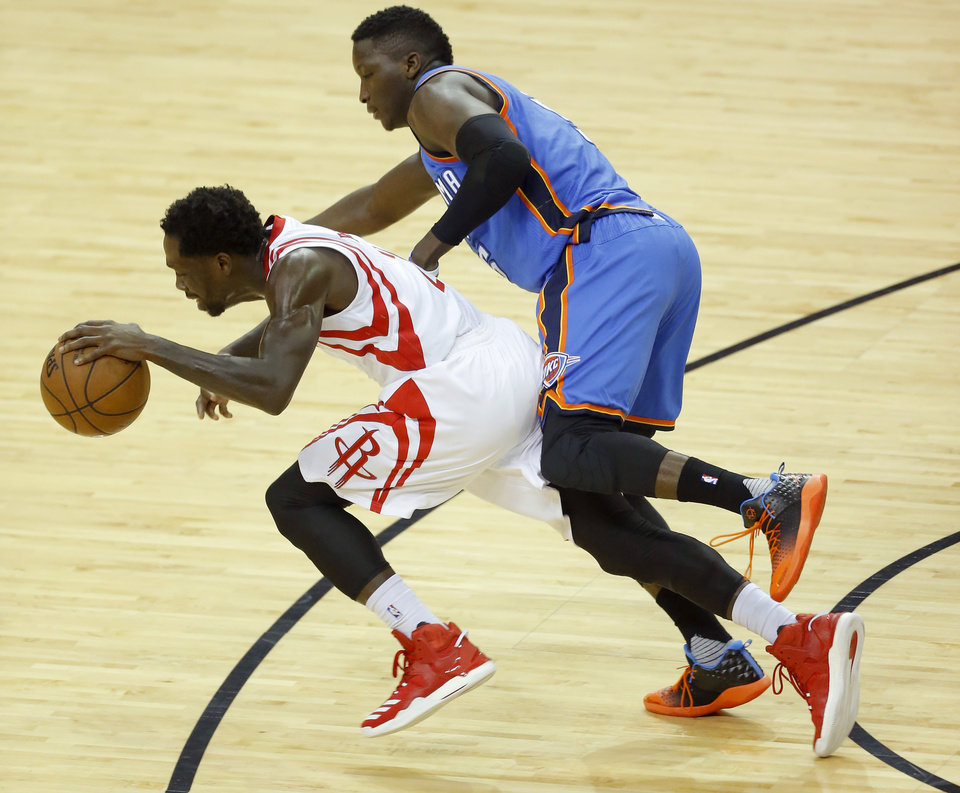 Photo - Oklahoma City's Victor Oladipo (5) defends Houston's Patrick Beverley (2) during Game 2 in the first round of the NBA basketball playoffs between the Oklahoma City Thunder and the Houston Rockets at the Toyota Center in Houston, Texas,  Wednesday, April 19, 2017.  Photo by Sarah Phipps, The Oklahoman