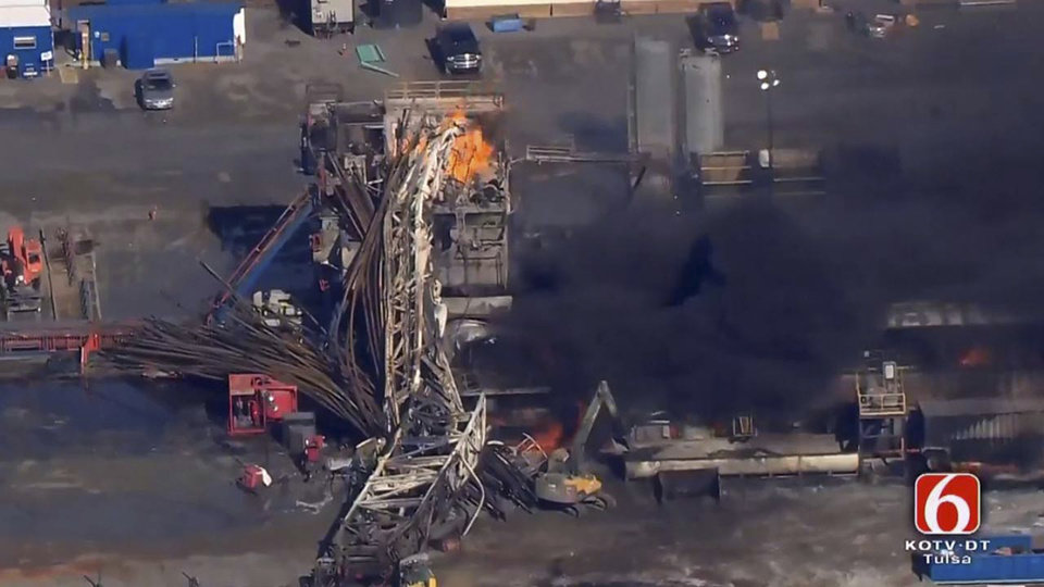 Photo -  In this photo provided from a frame grab from Tulsa's KOTV/NewsOn6.com, fires burn at an eastern Oklahoma drilling rig near Quinton on Monday. Five people are missing after a fiery explosion ripped through a drilling rig, sending plumes of black smoke into the air and leaving a derrick crumpled on the ground, emergency officials said. [Photo by Christina Goodvoice, KOTV/NewsOn6.com via AP]