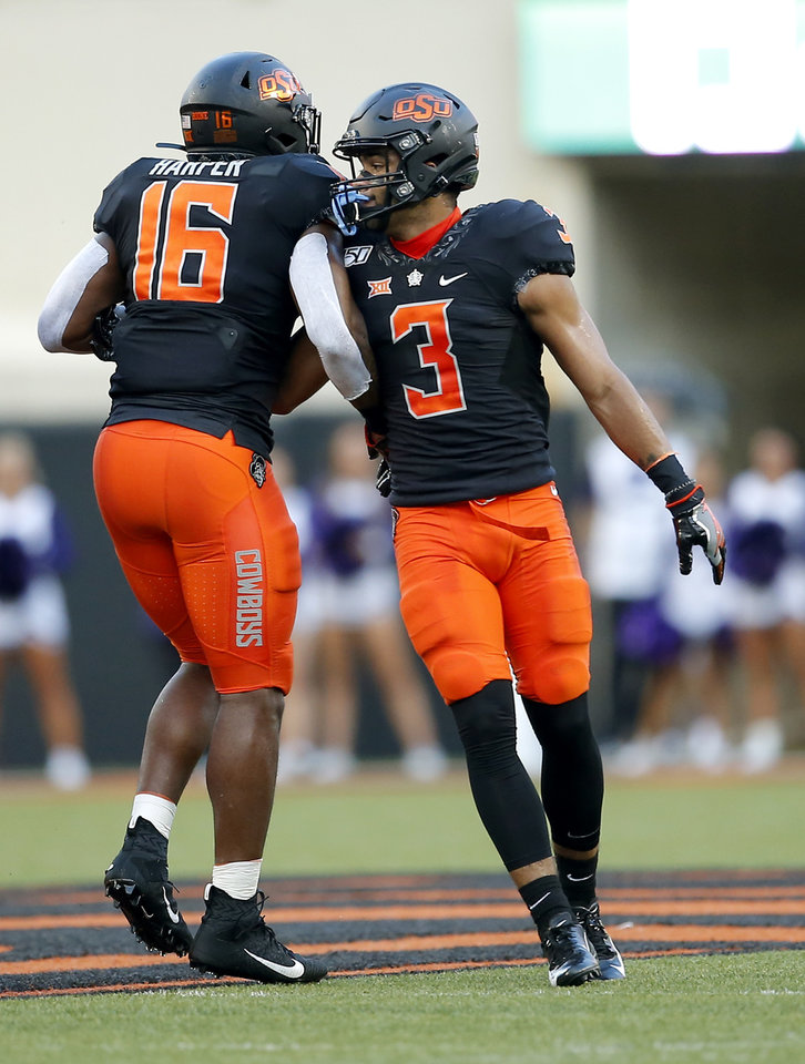 Photo - Oklahoma State's Devin Harper (16) and Tre Sterling (3) celebrate a play during the college football game between the Oklahoma State Cowboys and the Kansas State Wildcats at Boone Pickens Stadium in Stillwater, Okla., Saturday, Sept. 28, 2019.  OSU won 26-13. [Sarah Phipps/The Oklahoman]