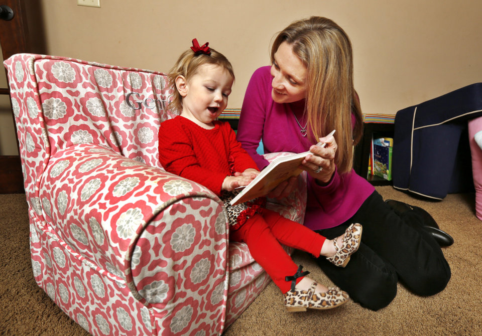 Photo - 21 month-old Gentry Knight reading a book with her mom Jennifer Knight in their home in Edmond Friday, Feb. 20, 2015. Gentry survived open heart surgery for a rare heart disorder. Photo by Paul B. Southerland, The Oklahoman