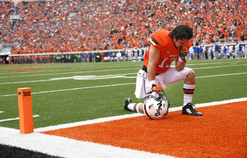 Photo - Oklahoma State's David Glidden (13) takes a moment before a college football game between the Oklahoma State University Cowboys (OSU) and the Kansas Jayhawks (KU) at Boone Pickens Stadium in Stillwater, Okla., Saturday, Oct. 24, 2015. Photo by Sarah Phipps, The Oklahoman