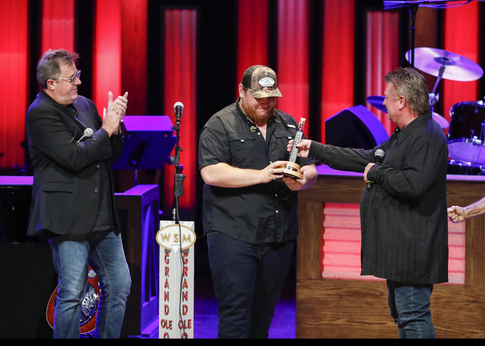 "Photo - Vince Gill, left, and Joe Diffie, right, welcome Luke Combs to the Grand Ole Opry at ""Luke Combs Joins the Grand Ole Opry Family,"" Tuesday, July 16, 2019, in Nashville, Tenn. (Photo by Al Wagner/Invision/AP)"