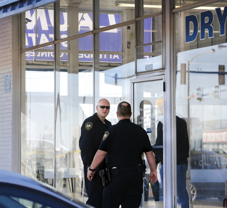 Photo - Two officers stand outside the front door of the laundry business. The bodies of a man and a woman were found inside the Laundry Station, 4000 SE 15, in Del City, shortly before it opened for business Monday morning, Jan. 23, 2017, according to a police spokesman.  A customer arrived around 6:30 a.m. and saw both victims lying dead inside the business. Police Maj. Jody Suit said the double homicide could be part of a robbery. The names of the victims were not released and no arrests were reported. The business usually opens at 7 a.m. on Mondays, a sign on the door reads. Photo by Jim Beckel, The Oklahoman
