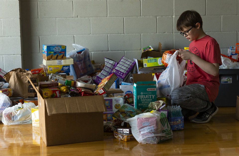 Photo - Volunteer Ryder Watts collects items for victims of the tornado at the Red Cross Shelter inside the Jenks Simmons Fieldhouse in El Reno, Okla. on Monday, May 27, 2019. The EF3 tornado hit the area on Saturday night killing two people and injuring many others. [Chris Landsberger/The Oklahoman]