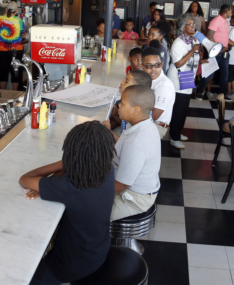 Photo - Children sit at the counter inside Kaiser's Grateful Bean Cafe to reenact the first Katz Drug Store sit-in, one of the first civil rights protests in the nation, as Joyce Henderson, upper right, speaks in Oklahoma City, Saturday, Aug. 18, 2018. The sit-in was to commemorate the 60th anniversary of the Katz Drug Store sit-ins. The first Katz Drug Store sit-in happened on August 19, 1958. Henderson participated in later sit-ins at Katz Drug Store. Photo by Nate Billings, The Oklahoman