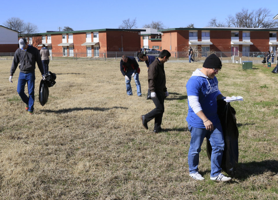 Photo -  Chase Parsons works with a group of volunteers to clean up the grounds at local apartment complexes and interact with residents as part of an Adopt-a-Block outreach program organized by the Oklahoma City Dream Center. [Photo by Paul Hellstern, The Oklahoman]